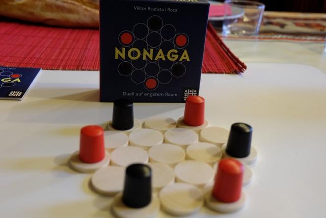 Premier sorti, Nonaga. Un jeu qui me fait penser à l'un de mes protos : regrouper ses pions sur un plateau. Le reste diffère, mais voilà, l'essentiel est là. Donc, comme vous l'avez compris, dans ce jeu, chacun des deux joueurs va essayer de recoller ses 3 pions où que ce soit, en respectant quelques règles basiques : à son tour on déplace un de ses pions au plus loin qu'il le peut sur la ligne de son choix, puis on déplace un disque (=case de plateau), pour peu qu'il n'ait pas été déplacé par l'adversaire au tour d'avant. Et c'est tout !!! Pur de chez pur, non ?
