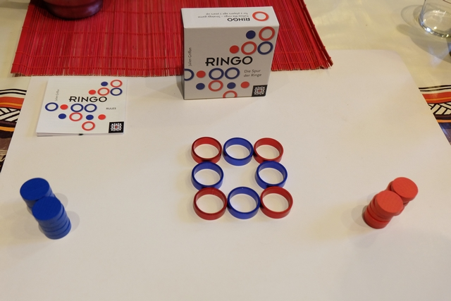 Au départ, on étale sur la table un carré de 3 par 3, constitué d'anneaux métalliques du plus bel effet, en alternance bleus / rouges. Joris jouera les rouges et moi les bleus. A son tour, le joueur actif doit poser un de ses disques dans un anneau quelconque, puis déplacer cet anneau où il le souhaite, à côté d'un autre anneau quelconque, orthogonalement.