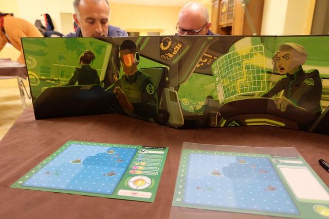 Ce jeu, atypique, se joue avec deux équipes qui se trouvent face à face. On essaie d'équilibrer les équipes, mais l'une d'elles peut ne comporter qu'un joueur. Pour notre première partie, nous sommes trois, donc Yohel joue avec Hérvé, pour l'équipage bleu), tandis que je joue seul pour l'équipage vert. Chacun des joueurs a un rôle spécifique : Capitaine, pour déplacer le sous-marin, et Détecteur, pour localiser le sous-marin adverse et tenter de le couler. Et oui, on est un peu comme dans la bataille navale de notre enfance, sauf que là il n'y a pas que de la chance...