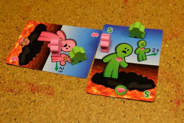 Mise en place de la partie, avec une carte jouée chacun, puisqu'on est deux, Leila (avec les roses) et moi (avec les verts). Chacun a posé sur sa carte un meeple à sa couleur et en a posé un autre sur la carte de l'autre joueur. La -vraie- partie va pouvoir débuter...