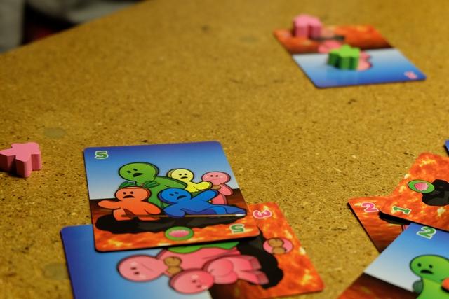Chaque carte comporte une ou plusieurs couleurs de meeples : évidemment les joueurs concernés placent autant de meeples qu'indiqués lorsque leur couleur apparaît.