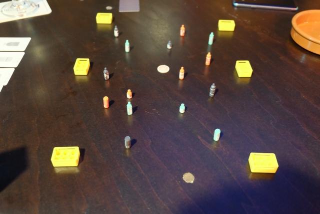 La mise en place du jeu, avec cette règle retenue, consiste en une délimitation du terrain de jeu par les 6 caisses jaunes. A l'intérieur, placées aléatoirement, les bouteilles des joueurs sont disposées debout. On en place 5 chacun, la 6ème, la petite canette, servant de projectile qui sera lancé à partir de la pièce de 500 yens centrale. Le but du jeu est de faire tomber ses propres bouteilles, une à une, en fonction de l'ordre des cartes qu'on devine à gauche.