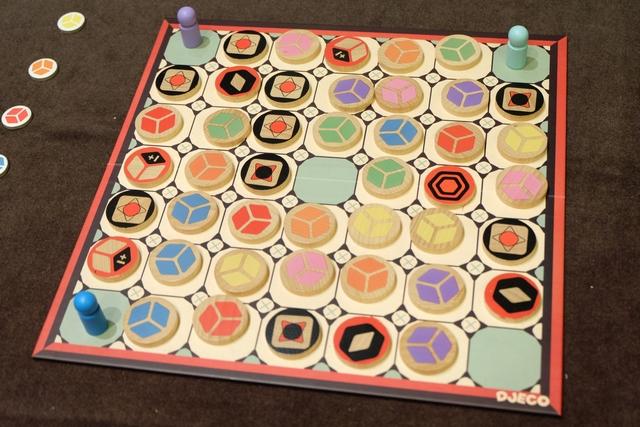 Au départ, le plateau est installé totalement au hasard avec les disques de bois colorés et les joueurs positionnent leur pion (bleu pour Maitena, violet pour Joris et turquoise pour moi) sur l'un des sommets du carré principal. Ensuite... et bien ce sera une sorte de course à la collecte de disques (cubes en 3D si on veut bien regarder les disques...) dans un certain ordre en procédant à des déplacements comme le cavalier aux échecs : 2 vers l'avant + 1 sur le côté. Allez, enclenchez la réflexion à 0 hasard, c'est parti !!!