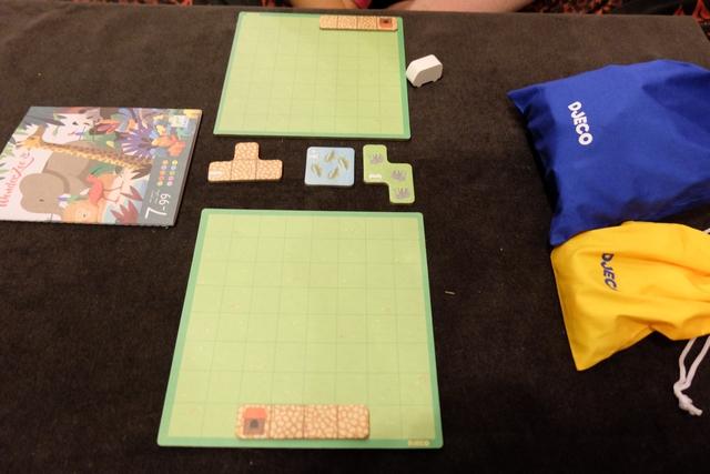 Chaque joueur dispose d'un plateau individuel sur lequel, à la manière d'un Tetris, il va essayer de placer au mieux des tuiles de terrain pour construire le zoo le plus intéressant pour les visiteurs. Au centre de la table, il y a trois tuiles (une de plus que le nombre de joueurs) avec un premier choix pour le premier joueur, avec le bus blanc (Leila donc pour ce premier tour), avant que l'autre joueur prenne une des deux tuiles restantes. L'idée principale est de réussir à placer des chemins qui vont passer près d'enclos (vert, bleu ou jaune) avec des animaux, pour que des visiteurs (meeples colorés piochés dans un le sac jaune ci-dessus) viennent les admirer en fonction de leur couleur.