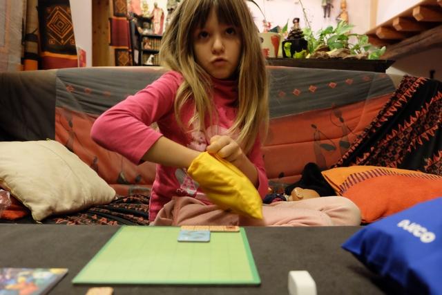 Leila a opté pour la tuile bleue carrée qu'elle a placé totalement où elle le souhaitait sur son plateau et elle pioche un meeple du sac car cette action était également inscrite sur la tuile.