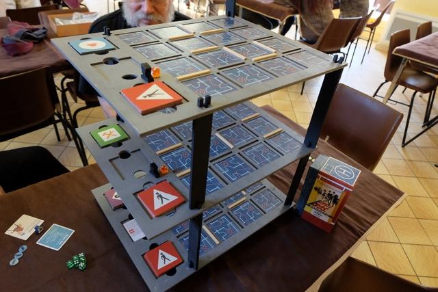 Les tuiles ont été positionnées comme prévu, étage par étage, avec la pile de cartes de chaque garde sur le niveau correspondant. Le garde du bas a été également placé ainsi que son dé de destination, orange, de valeur 1. Et, enfin, chacun de nous a pris un personnage au hasard et nous avons choisi la position de l'escalier permettant d'entrer au niveau 1 de la banque... Ça va démarrer... J'en suis tout ému ! ;-)