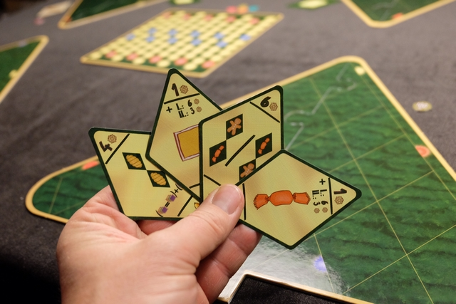 Ma main de cartes d'objectifs pour cette partie, sachant qu'une carte sera défaussée. Je me vois bien lancer une sorte de course aux bonbons, en y ajoutant des bonshommes en pain d'épice au-dessus ou en-dessous d'eux. Enfin, ce sera pour les manches 2 et 3, histoire d'avoir le temps de prendre de l'avance sur ces points lors de la première...
