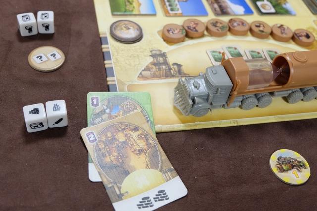Petit exemple de mon premier tour. J'ai lancé les dés plusieurs fois et obtenu deux flammes rouges (non visibles sur la photo). Avec les faces restantes, combinées à une tuile ronde de Tuarek (m'offrant deux faces de dés de mon choix en plus), j'ai récupéré deux bidons de kérosène + construit les deux cartes ci-dessus. Ça va être au tour de Romain. Et ainsi de suite jusqu'à la fin de partie.