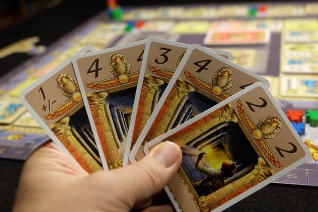 En début de partie, chacun récupère une main de 5 cartes de déplacement qu'il laisse obligatoirement dans l'ordre de la pioche. C'est fondamental et c'est le coeur du jeu : on ne peut jouer qu'une des cartes placées aux extrémités de sa main (donc la 1 +/- ou la 2 pour moi ci-dessus), sachant qu'ensuite, après s'être déplacé, on doit rajouter une carte de la pioche au milieu de sa main (au milieu de ses 4 cartes restantes). Très innovant, ce système de déplacement, un peu délicat sans se tromper pendant quelques tours, se révèle particulièrement jouissif, obligeant à prévoir un tour ou deux dans sa tête. Et toute carte piochée mettra au moins 2 tours à devenir utilisable...