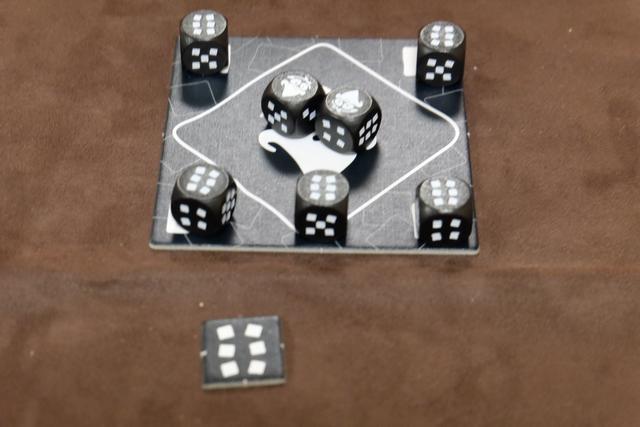 A son tour, le joueur actif lance les 7 dés et doit conserver les corbeaux obtenus, puis décide quelle valeur de dé il conserve : il place les dés concernés sur les cases blanches dans les coins. Ci-dessus, j'ai gardé les 6. Ensuite, il rejette les dés restants et conservera obligatoirement les corbeaux et les faces de la même valeur qu'auparavant (interdit d'en changer). Et ainsi de suite, jusqu'à ce que 4 dés identiques aient été conservés ou 3 corbeaux placés au centre. Ci-dessus, j'ai obtenu 5 fois la valeur 6, donc je récupère un jeton de valeur 6, mais comme j'ai dépassé les 4 dés, je prends aussi la tuile Murphy. Si c'était les corbeaux qui avaient atteint 3, j'aurais pris un marqueur de poisse de la réserve (ou ceux présents vers les corbeaux s'il y en avait eu). J'y reviens...