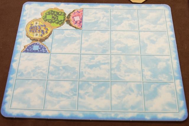 Voici mon plateau individuel, à peu près le même que celui des autres joueurs (quelques variations sur les deux îles complètes et les deux portions non terminées). Chaque case carrée dessinée représente un emplacement pour un pion habitant de la couleur correspondante (vert, rose ou bleu), sachant que le cas des villes jaunes est complètement différent : on les peuple uniquement via la conversion d'énergie (transfert de pions bleus depuis les îles de cristaux bleus pour obtenir 1 PV par pion).