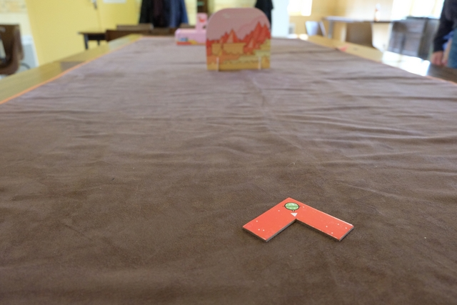 """Nous avons rassemblé 4 grandes tables à notre salle de réunion habituelle et installé un immense tapis pour symboliser la zone de jeu. Puis, nous avons opté pour une partie de découverte avec les 9 premiers trous suggérés dans la règle. Ci-dessus, voici le trou n°1, mis en place, avec la zone de tee, représentée par le L rouge ci-dessus, autorisant le joueur actif à propulser sa """"balle"""" à l'intérieur de l'angle droit. A noter qu'il y a un grand obstacle plus avant et que vous pouvez apercevoir le trou tout au bout de la table..."""