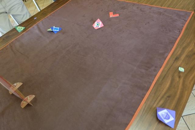 """Les sortes d'avions en carton, carrés, que vous pouvez voir étalés sur la table, sont les fameuses """"balles"""" de golf projetées par les joueurs ! Non ? Si, si... La technique de projection est celle d'une pichenette exercée sur l'arrière de la """"balle"""", côté relevé. L'auteur indique 4 techniques similaires pour faire avancer sa """"balle"""", soit en la frappant droite, de côté gauche, ou droit, ou alors, carrément par-dessus avec une force certaine, sans oublier une sorte de projection avec deux doigts de bas en haut. En clair, on doit s'améliorer de partie en partie, car la technique existe vraiment et peut se maîtriser petit à petit..."""