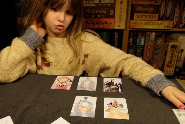 A son tour, le joueur actif, ici Leila donc, place une des deux clés prises au début de son tour et une des cartes de son Notebook sur une des 5 piles de cartes puis pioche une carte dans les deux tas adjacents qu'il place dans son Tunnel (la zone au-dessus de son Notebook). Ensuite, le joueur actif peut appliquer le pouvoirs des cartes piochées et, ensuite, décider de recommencer ou de s'arrêter afin de sécuriser les cartes de son Tunnel. S'il recommence, il peut soit piocher à nouveau deux cartes dans les tas adjacents à la clé déjà posée, soit placer une nouvelle clé (sa deuxième donc), ainsi qu'une carte face visible de son Notebook sur un autre tas pour piocher les deux cartes adjacentes à celle-ci. Quel est le risque ? Que le Tunnel s'effondre et de perdre les cartes qui s'y trouvent  ! Ceci survient dès que 3 cartes identiques se trouvent dans le Tunnel...