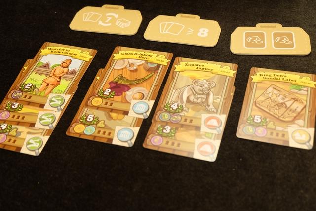 Au centre de la table, nous étalons 8 carte, classées par continent et par époque (de la plus ancienne en-dessous à la plus récente au-dessus, au contraire de ce qui est écrit dans les règles...). Ce sont les zones de fouilles sur lesquelles nous allons pouvoir envoyer nos explorateurs. Au-dessus, on tire au hasard 3 valises de super outils (équivalentes à des jokers si on en satisfait les conditions) sur les 5 contenues dans la boîte.