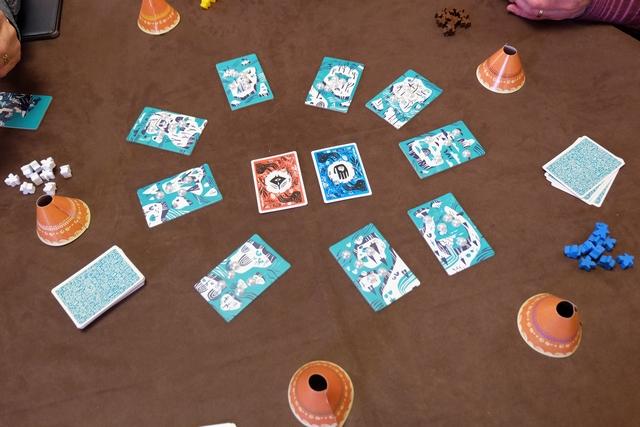 Sur la table, sont étalées 9 tuiles d'îles sur lesquelles vont être placés 3 pions par joueur. Au centre, figurent les deux cartes de couleur, indiquant la couleur des cartes qui seront décomptées en fin de tour, sachant que : il y a 5 tours en tout et, surtout, qu'une carte sera retournée par le Shaman (au dos de la rouge, il y a la couleur orange ; au dos de la bleue, la violette).