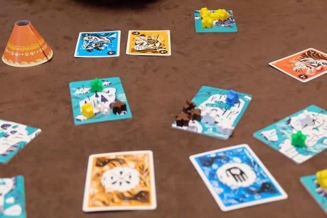 Petit exemple de joli coup, un peu vicieux, qu'on peut mettre en œuvre... J'ai moult cartes orange dans ma main. Yohel, placé en face de moi, est le Shaman. Je tente de lui graisser la patte en posant devant lui une carte visible orange indiquant +2. Ainsi, j'espère qu'il ne retournera pas la carte orange... Et, joli coup complémentaire orchestré par Fabrice : il ajoute, devant Yohel, une carte bleue marquée -3 ! Du coup, Yohel a encore beaucoup plus envie de retourner la carte bleue sur son côté violet...