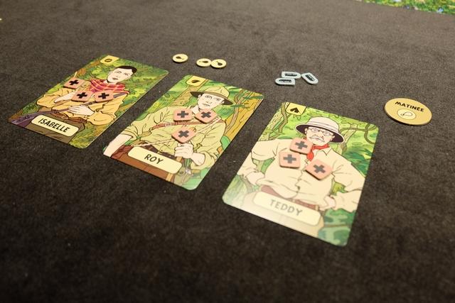 Je choisis les 3 explorateurs ci-dessus pour découvrir le jeu, en en prenant un de chaque compétence, comme spécifié dans la règle : Isabelle sait s'orienter, Roy connaît la jungle et Teddy sait installer des campements (en haut à gauche des cartes). Chaque explorateur dispose de 3 points de vie, placés sur eux. Enfin, l'équipe a en sa possession 3 unités de nourriture et 3 unités de munitions.