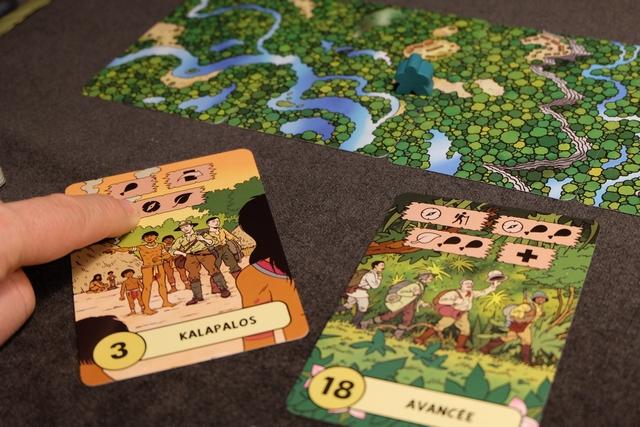 """Petit exemple d'utilisation d'une carte """"amie"""" remportée en début de matinée : la carte Kalapalos. Je l'avais gardée pour ses deux compétences (orientation et jungle) et, ci-dessus, je la défausse comme requis sur la carte Avancée afin de faire progresser mon meeple vert d'une carte sur le paysage en haut. J'aurais pu, tout aussi bien, opter pour deux nourritures (en la défaussant) ou un point de vie (sa,s la défausser). Mais le but du jeu m'incite à aller vite, tant que faire se peut..."""