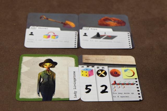 Chaque joueur a pris un personnage, le vert baptisé Lady Livingstone pour moi, et une carte aléatoire de pouvoirs (la mienne : Scout). Chaque carte de pouvoirs indique le nombre de dés que le joueur possède, le nombre de cartes outils qu'il pioche, le pouvoir spécial (la roue) et la capacité de relancer des dés (tout le monde a celle-ci... jusqu'au moment où cette capacité sera annulée !). J'aime beaucoup les illustrations qui me rappellent ceux de L'Auberge Sanglante de chez Pearl Games...