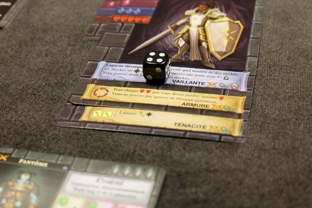 Ayant découvert un fantôme de niveau 4 derrière une porte fermée, je stocke un dé noir sur mon bandeau de Capacité héroïque : quand je le souhaiterai, je pourrai le lancer avec les autres auxquels j'ai droit.
