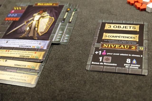 Avec mes 7 XP, je passe au niveau 2, ce qui m'apporte plein de bonus : un nouveau cube de potion, un dé noir, la possibilité de placer jusqu'à 3 objets et 3 compétences. Je vais défausser mes cartes d'XP évidemment...