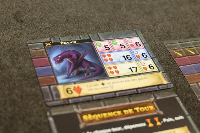 Voilà à quoi ressemble le fameux dragon violet qui m'attendait : 6 PV et de grosses demandes en dés jaunes et bleus pour qu'il ne me blesse pas trop (ça tombe pas mal...). A noter que pour le blesser, il me faudra mettre exclusivement (pas de dé noir) un dé rose de valeur 6, un dé bleue de valeur et un dé jaune de valeur 6. Grâce à mes compétences et mes 9 PV, je ne ne me sens pas trop inquiet... Ça pourrait même être plié en 2 rounds !!!