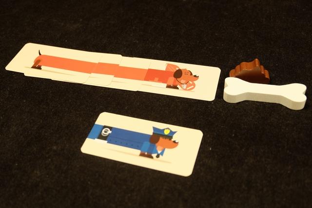 Un peu comme lors de notre partie plantée, j'ai un peu l'impression qu'on a intérêt à jouer beaucoup de ses cartes, histoire d'en repiocher pour en avoir 5 et, du coup, de pouvoir se focaliser sur telle ou telle couleur. Le truc, c'est que, parfois, on ne va pas jouer toutes les cartes d'une même couleur de suite, histoire que l'adversaire en rajoute un peu, sans le prendre espérons-le ! De même, il faut savoir ne pas se contenter de trop petits chiens pour éviter de se ramasser, et de conserver, la crotte qui fait perdre 6PV en fin de partie (plus petit chien construit). Au contraire, l'os en rapportera 6PV pour le plus long chien. En cas d'égalité, le nouveau chien construit fait remporter la crotte ou l'os. Ci-dessus, au premier tour, j'ai posé mes 5 cartes et terminé puis empoché un chien rouge de longueur de corps 3 : donc chien le plus long et le plus court à la fois.