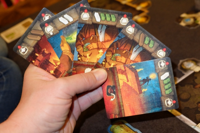 Chaque joueur reçoit une main de 5 cartes au départ afin de tenter de récupérer la tuile mise en jeu pour ce tour. Chaque carte comporte deux informations : en haut, le nombre de dés et leur couleur si elle est jouée au début du tour (associée à autant qu'on le souhaite avec le même symbole en haut) ; en bas, l'effet de la carte si elle est jouée grâce à un dé avec un naga (serpent) en cours de tour.