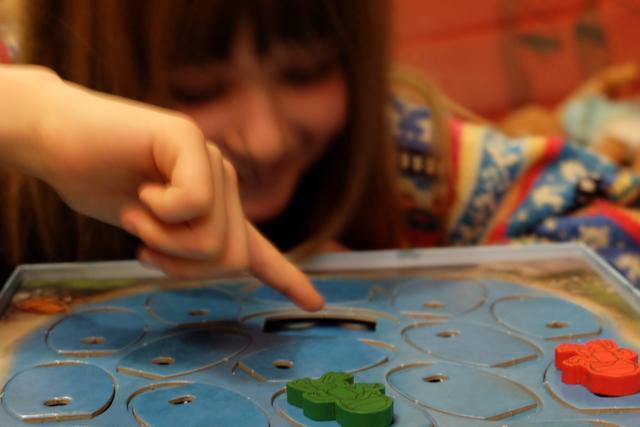 """Le jeu est vraiment très rigolo, surtout qu'avec nos gros doigts d'adultes, on est clairement défavorisé par rapport à ceux de Leila ! A noter, aussi, que la forme ronde des jetons est ultra frustrante puisque l'on ne peut pas vraiment espérer rapprocher un jeton éloigné en se servant d'un autre : ça """"n'accroche"""" pas..."""