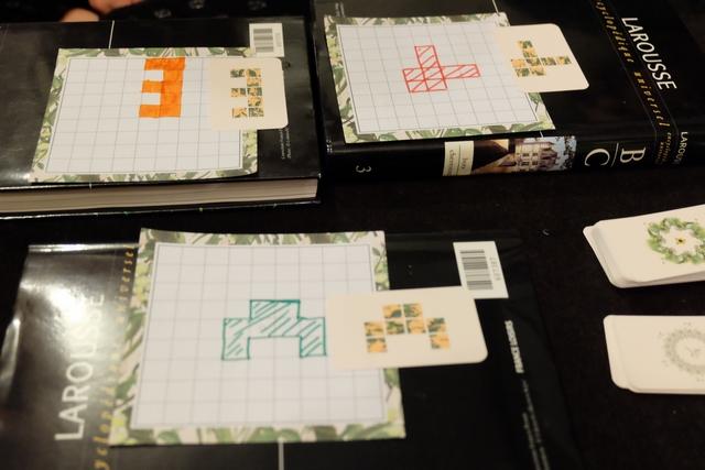 Avant de démarrer vraiment la partie, chacun doit dessiner une forme différente prise dans le pioche, superposée à la case centrale de sa fiche. Voici, donc, les réalisations initiales des trois joueurs attablés ce soir...