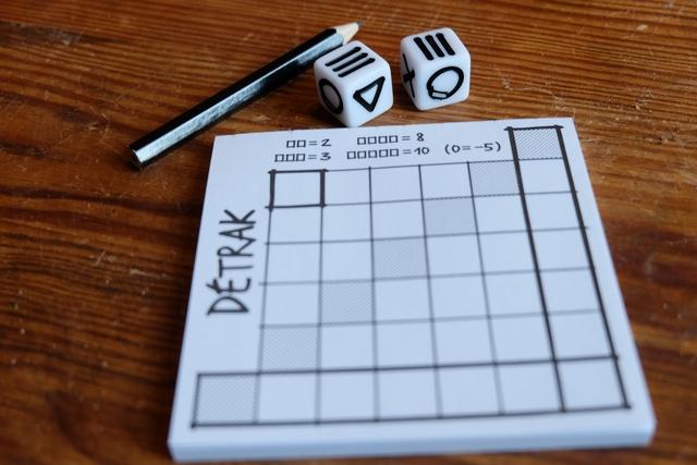 Le matériel est carrément minimaliste : un bloc (enfin plutôt deux), une paire de dés spéciaux (mais en fait il y a 6 faces différentes, donc pas si spéciaux que ça) et un crayon par joueur. J'ai, personnellement, ajouté une gomme dans la boîte et, hop, nous voilà en présence d'un bien bon jeu dans la grande mode actuelle des Roll& Write...