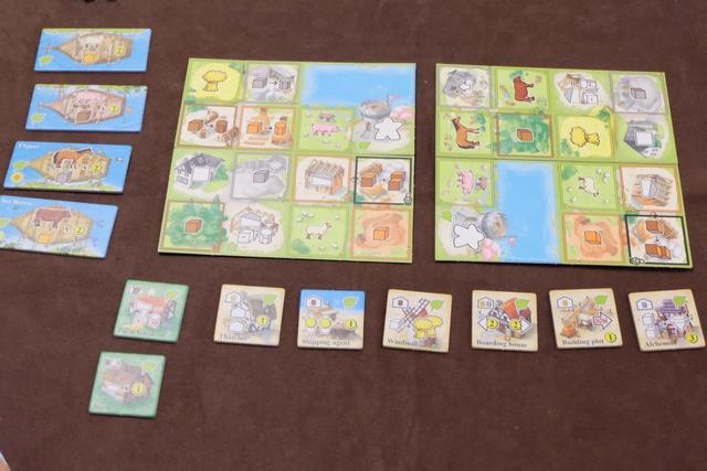 Au centre de la table, on installe autant de plateaux de paysage que de joueurs (donc 2 aujourd'hui car nous sommes 2 à jouer). En-dessous, on a étalé 8 tuiles de printemps (avec la feuille en haut à droite) car c'est la première saison sur les 4 que comptera la partie. A gauche, vous pouvez voir les 4 bateaux étalés pour cette saison, chacun d'eux pouvant être mis sur un des plateaux de paysage quand un joueur décide de réaliser une action de port.
