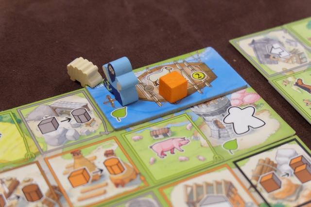 Petit exemple du fonctionnement du keyple bleu que l'on a chacun : en le posant sur la zone de rivière d'un plateau de paysage, j'y place aussi l'un des quatre bateaux tirés au hasard en début de saison, ce qui me permettra de faire deux fois une action bateau (collecte ou vente de ressources) car c'est le bon keyple que j'y ai placé. Si j'avais mis un keyple orange, par exemple, je ne l'aurais fait qu'une fois. Ci-dessus, donc, je décide de vendre un mouton, pour un gain immédiat de 2PV, et de récupérer un cube d'argile (orange) que je vais rajouter sur mon plateau individuel.