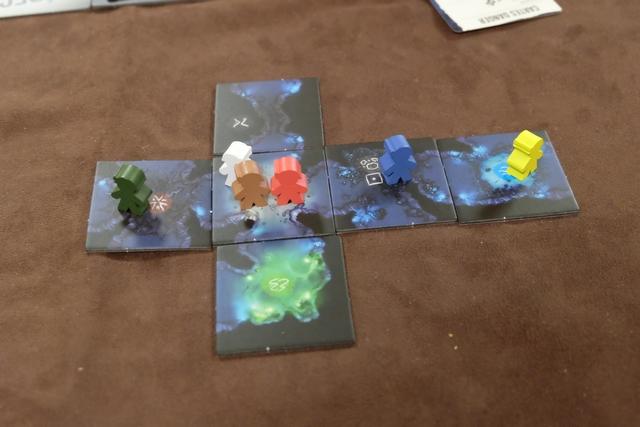 Voici la vue en fin de premier tour. Que s'est-il passé ? J'étais premier joueur et j'ai d'abord joué le personnage marron puis le vert : avec 2 points d'action par personnage, j'ai exploré deux tuiles avoisinantes avec le marron (en ayant le droit de choisir entre deux tuiles à chaque fois, c'est son pouvoir) puis le vert s'est déplacé sur la tuile difficile (grâce à son pouvoir de jet de talent à +1). Ainsi de suite avec les autres personnages, à raison de 2 points d'action par personnage. Ensuite, s'il y avait eu des Horreurs en jeu, elles se seraient déplacées vers la proie la plus proche. Enfin, on a tourné une carte de danger indiquant qu'un Horreur apparaissait si une case en comportait le symbole (ce qui n'était pas le cas). Je passe le marqueur de premier joueur à Fabrice et c'est reparti pour le deuxième tour...