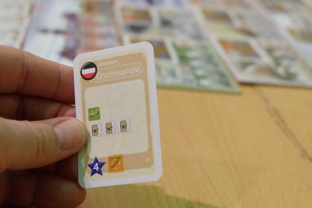 En début de partie, chaque joueur obtient une première carte de commande qu'il a sélectionnée parmi deux. Voici la mienne : l'Allemagne attend que je lui fournisse une unité de thé et trois unités de soie sauvage. Si j'y parviens, j'empocherai 4 PV sur la piste et une unité de marchandise importée. A noter que, lorsqu'on termine deux cartes du même pays (que ce soit des commandes ou des technologies), on récupère un agent étranger de ce pays. Ces derniers permettent la réalisation d'une action supplémentaire à un moment donné. Pas crucial mais ça peut booster les choses en fin de partie d'après ce qu'on a m'a dit...