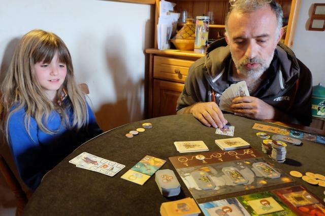 Nous sommes en phase de résolution de la quatrième manche. Alors que Leila se bat sur les cartes bleues pour avoir le plus grand total, je continue de jouer sur les petites cartes, pensant qu'il est plus facile, surtout à 5 joueurs, d'être celui qui a la plus faible que de totaliser le plus grand score. En analysant la chose, en effet, cela est très logique : une seule carte peut suffire pour avoir le plus petit total dans une couleur alors qu'il faut plusieurs pour avoir le plus grand. Sans compter que les cartes non stockées pour cela peuvent être des pièces ou des chiens. Donc, intérêts multiples !