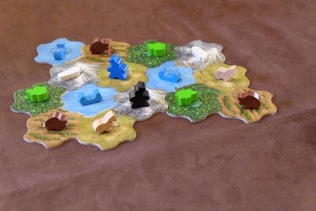 Voici le paysage pour cette partie, constitué d'autant de tuiles que de joueurs +1, donc trois aujourd'hui, avec les cinq types de terrain sur chacune. Fabrice a placé un indien bleu sur une plaine à chevaux, tandis que j'ai un des miens, noir, sur une zone de montagne. Il a récupéré un cheval et moi une plume d'aigle.
