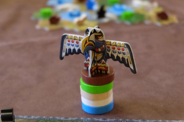 Étant premier joueur, je place le totem devant moi, constitué de 5 disques colorés correspondant aux couleurs des terrains. Au-dessus de ce totem, trône un magnifique aigle, version majuscule de celui qui parcourra la piste des saisons. Le système d'actions du jeu, basé sur un dépilement astucieux du totem, constitue le cœur mécanique du jeu et je ne vais pas me priver de vous en expliquer le fonctionnement ! Rendez-vous en-dessous de la photo suivante, à comparer avec celle-ci...