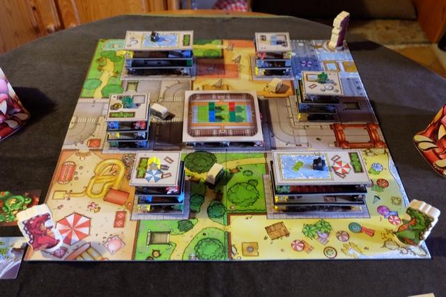Le jeu a été mis en place et pas en 3 minutes ! Rendez-vous compte : 7 immeubles de 2 à 4 étages avec des meeples pour soutenir les étages supérieurs ! Évidemment, le but du jeu de nos dinosaures sera de détruire un maximum d'immeubles, justement, en se nourrissant du béton (les étages) et les habitants abandonnés au sol (les meeples). Une filiation très claire avec le jeu vidéo de ma jeunesse...