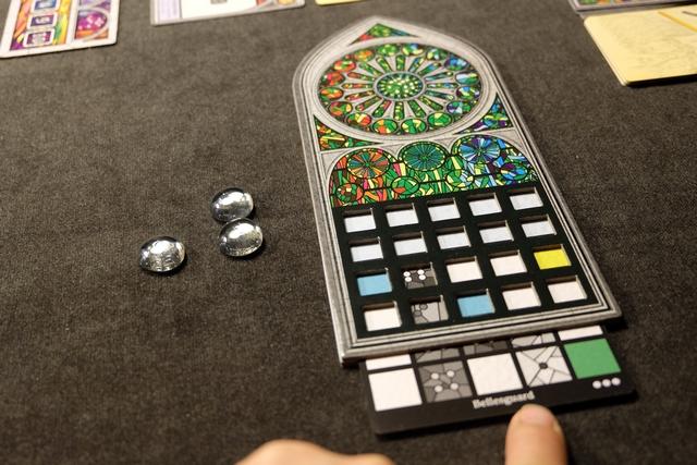 """Chaque joueur va créer son propre vitrail en insérant dans la fente du bas une carte de création inspirée de vitraux réels. Le système, ingénieux, permet de renouveler les parties de manière impressionnante (les cartes sont bifaces, avec divers niveaux de difficulté, symbolisés par les points en bas à droite, de 3 à 6, et avec le choix seulement entre deux cartes prises au hasard)... A noter que j'ai pris 3 pierres de faveur, utilisables pour """"tricher"""" avec certaines règles, car j'ai une carte de difficulté 3. Leila, elle, en a 5, mais une carte plus difficile à réaliser. Intéressant compromis..."""