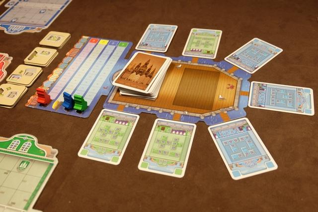 Dans le port de Copenhague, on a à notre disposition 7 cartes de façades prêtes à rejoindre notre main : 4 bleues et 3 vertes par le hasard de ce premier tour... Sur la gauche, la piste de PV, avec, comme but ultime, l'envie d'arriver le premier à 12, synonyme de victoire. Plus à gauche encore, les tuiles spéciales qu'on pourra récupérer en réussissant à recouvrir un blason (j'y reviens). Enfin, vous commencez à apercevoir la façade de chaque joueur, celle qu'il va tenter de compléter au mieux...