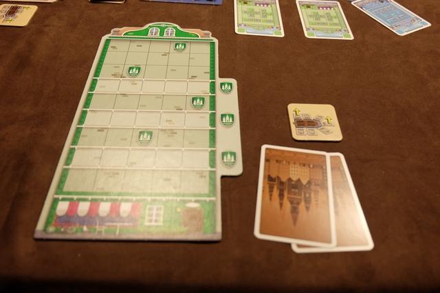 Voici, donc, ma façade verte, à compléter avec des parties de façades... pas forcément vertes ! Quel dommage que Queen Games ne tente pas de faire d'autres choix de coloris entre la couleur des joueurs et celle des pièces de jeu.... Chacun a une main de 2 ou 3 cartes (2 pour moi parce que je commence, 3 pour les autres à 3 joueurs) laquelle lui permettra d'ajouter de tuiles de façades dans sa maison. Le jeu est très simple, vous verrez... A noter la présence de blason sur certaines cases / lignes, ces fameux blasons qui permettront de profiter d'une action spéciale : prise d'une tuile spéciale OU prise d'une case de façade joker OU retournement des tuiles spéciales déjà utilisées.
