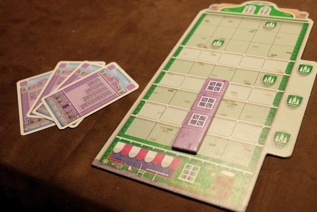 Petit exemple de l'un de mes premiers tours de jeu. J'avais le choix entre prendre deux cartes adjacentes sur le port (sans excéder une main de 7 cartes, sous peine de défausse) et construire une façade. C'est cette deuxième option que je retiens, laquelle me fait défausser 4 cartes violettes pour placer une façade de taille 4 violette. Limpide. Seule contraintes de construction : la tuile doit soit être au niveau le plus bas, soit reposer sur une tuile déjà posée quelle qu'en soit la couleur. Et c'est tout !