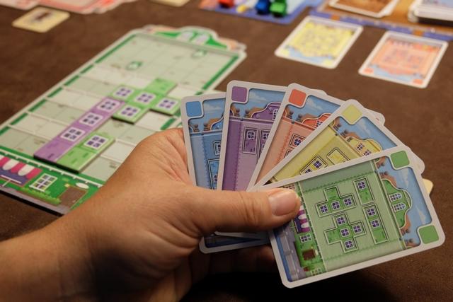 Ma main de cartes est complètement diversifiée. Qu'à cela ne tienne : l'une des tuiles spéciales permet de modifier la couleur des cartes jouées ! Sur la gauche, vous apercevez à quoi ressemble ma façade à cet instant-là. Il va me rester, en gros, à vous dire comment on marque des PV...
