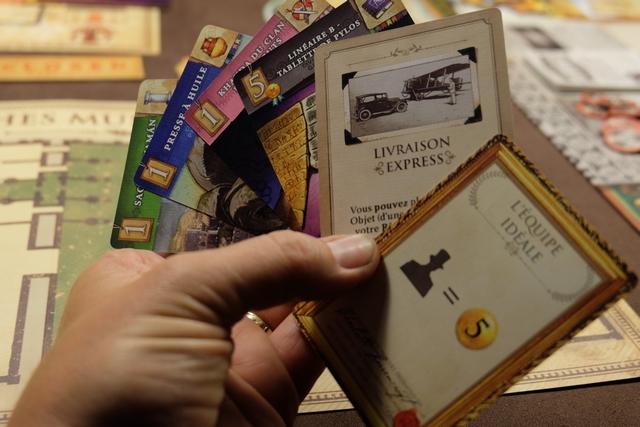 """En début de partie, chacun pioche une carte de chaque continent, pour un total minimal de 8 (valeur inscrite en haut à gauche). C'est pile mon total, donc ce n'est pas terrible. On y ajoute une carte de faveur (celle indiquant """"Livraison expresse"""" pour moi), laquelle apportera un bonus unique une fois dans la partie. Pour en avoir d'autres, il faudra atteindre les dizaines de PV (une à chaque passage de dizaine). Enfin, chacun sélectionne une carte de mécènes parmi trois piochées : j'opte pour celle-ci dessus, laquelle me rapportera 5 PV par expert recruté dans mon musée. Elle m'a l'air à la fois très forte (ça peut rapporter très gros à mon avis) et très facile à jouer (pas besoin de lier cet objectif à des objets spécifiques à exposer dans mon musée par exemple)."""