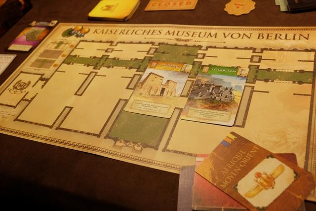 Voici mes actions du premier tour, sachant que j'ai été désigné premier joueur : j'ai importé une carte d'Afrique Moyen Orient, mes deux partenaires en prenant une chacune, d'où ma récupération de deux jetons de prestige (en haut à gauche de mon plateau), puis j'ai décidé d'exposer deux œuvres (une d'Egypte et une Inca) pour un paiement de 5 (4+1) que j'ai réalisé en défaussant, à gauche de mon plateau, une carte de valeur 5. Cette carte ne sera pas perdue pour autant, puisque l'action inventaire, alternative à la pose de cartes, permet de récupérer sa défausse. Il faut tester !